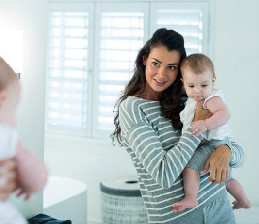 Körper nach der Geburt: Mama begutachtet sich mit Baby im Spiegel