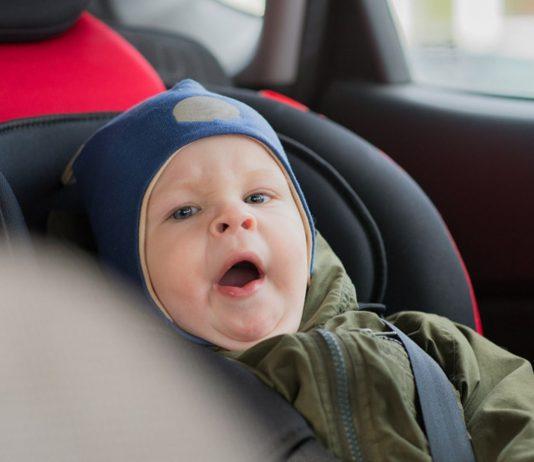 Winterjacken im Kindersitz: Junge im Auto