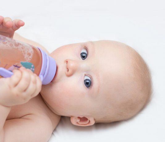 Baby trinkt Fencheltee aus Flasche