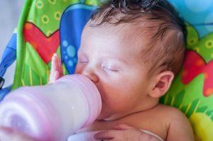 Baby trinkt im Halbschlaf