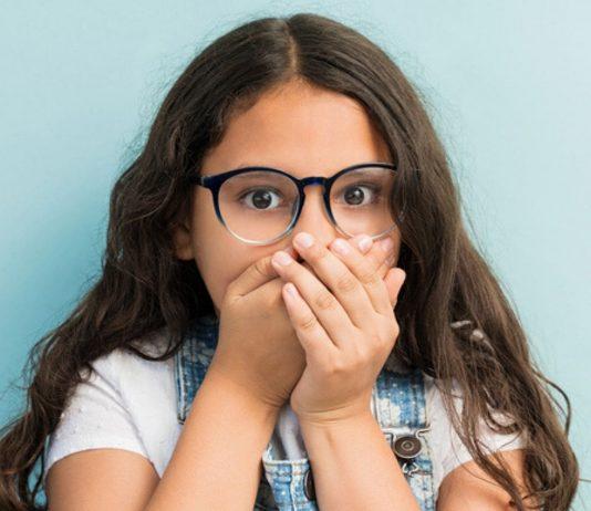 Black Stain Milchzähne schwarz: Mädchen hält sich Mund zu.