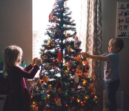 Christbaumschmuck Kinder basteln: Mädchen und Junge dekorieren Weihnachtsbaum