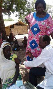 Dr. Etienne Mahangaiko beim Impfen einer Frau.