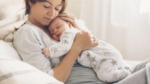 Kaiserschnittnarbe pflegen: Mama in bequemer Kleidung mit Baby im Bett sitzend