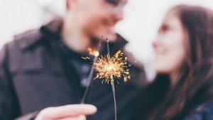 Schwanger an Silvester: Paar hält Wunderkerzen.