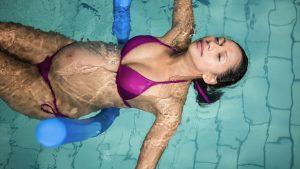 Schwangere treibt entspannt im Pool