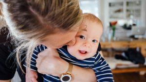Silvester Angst Kleinkind: Mama hält Baby und küsst es auf die Wange.