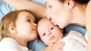 Tandemstillen von Baby und Kleinkind: Mama mit ihren zwei Kindern