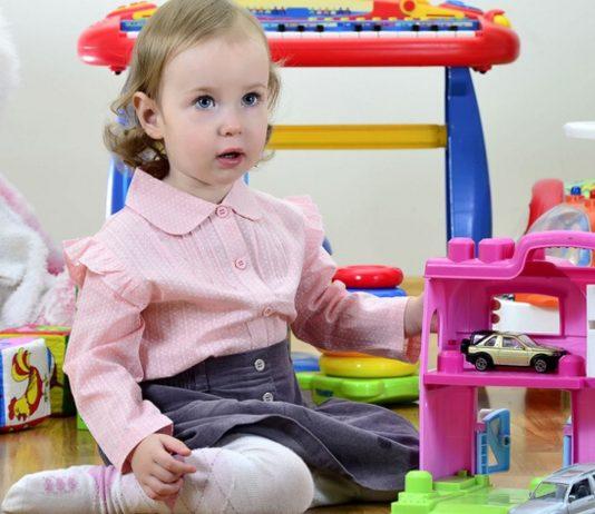 Stiftung Warentest Akustik-Spielzeug 2019: Mädchen inmitten von Spielzeug