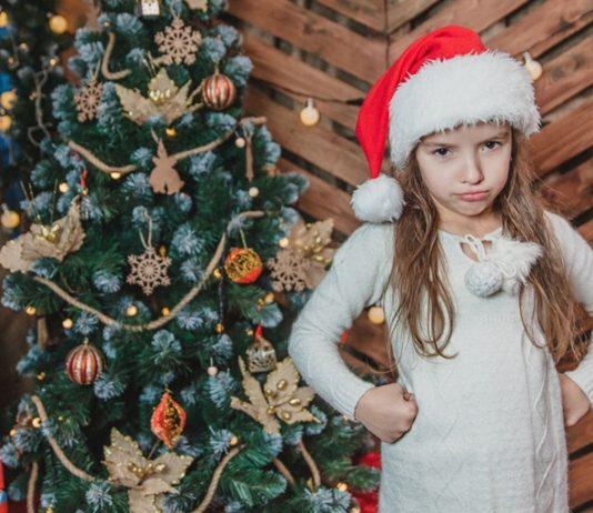 Enttaeuschtes Maedchen vor dem Weihnachtsbaum möchte Weihnachtsgeschenke tauschen