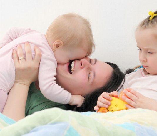 Mutter kuschelt mit Baby, Tochter schaut eifersuechtig zu - Eifersucht aufs Geschwisterchen ist haeufig ein Thema