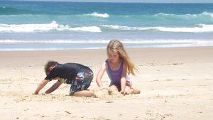 Kinder spielen im Familienurlaub am Strand