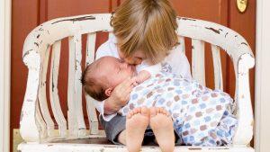 Grosser Bruder haelt und kuesst Baby: Bei Eifersucht aufs Geschwisterchen kann es helfen, dem grossen Kind Verantwortung zu uebertragen