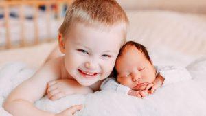 Grosser Bruder kuschelt stolz mit kleinem Geschwisterchen
