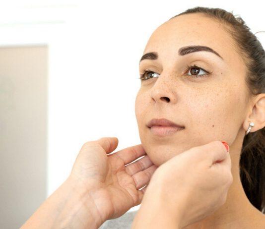 Schilddrüsenunterfunktion Schwangerschaft: Arzt tastet Hals einer Frau ab