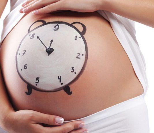 Schwangere mit aufgemalter Uhr auf dem Babybauch