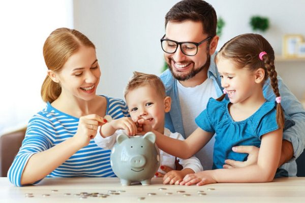 Familie mit Sparschwein: Mit unseren Spartipps für Familien bleibt am Monatsende mehr übrig