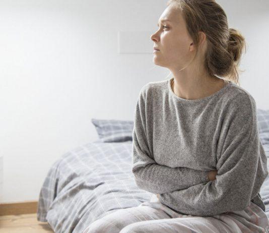 Eileiterschwangerschaft: Frau mit Unterleibschmerzen sitzt auf Bett
